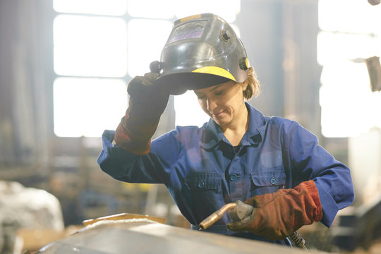 Waist up portrait of smiling woman welding metal while working at industrial plant, copy space