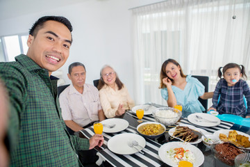 Man takes photos with his family in dining table