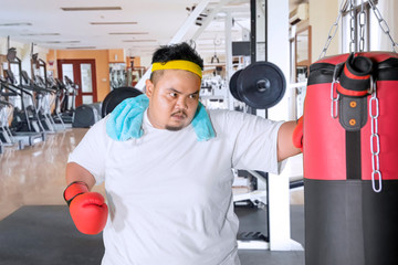 Overweight man hits a boxing bag in gym center