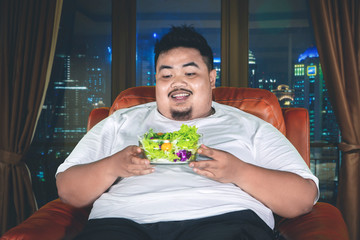 Overweight man holds a bowl of vegetable salads