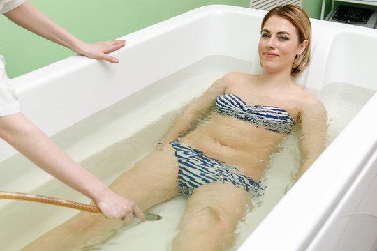 Specialist applynig hydrotherapy in bath. Underwater hydromassage in beauty salon