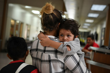 Paola, an asylum seeker from Honduras, carries four year-old son Jesse as they wait in a ticketing line with fellow migrant families recently released from detention at a bus depot in McAllen