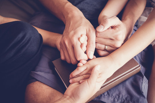 children holding hands and praying with their parent at home, family worship online, Having faith and hope.