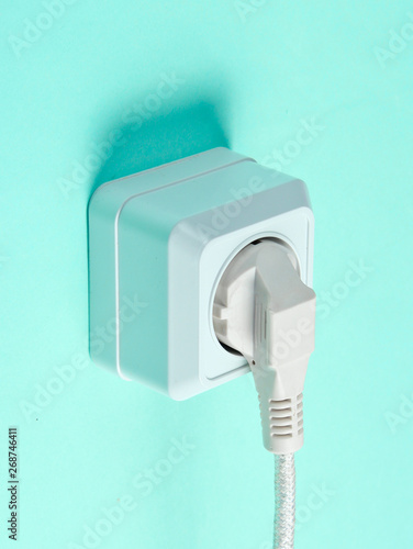 White cable plugged into power outlet on blue wall background