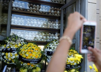 "A woman takes a picture at the Choeung Ek memorial during the annual ""Day of Anger"" where people gathered to remember those who perished during the communist Khmer Rouge regime, outskirts of Phnom Penh"
