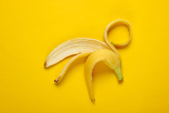 Minimalism fruit concept. Banana skin on yellow background. Top view
