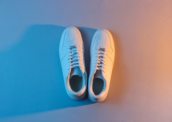 White sneakers with neon light. Top view. Minimalism