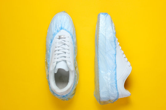 White sneakers in boot covers on a yellow background. Top view. Minimalism