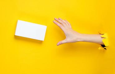 Female hand takes white box through torn yellow paper. Minimalistic creative fashion concept