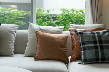Gray and brown pillows over sofa and window. Living room decoration.