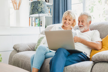 Couple senior using computer laptop on sofa at home for online shopping, surfing internet