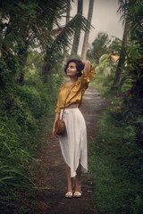 A girl in a white dress on the path between the palm trees. Bali trip. Travel, adventure.