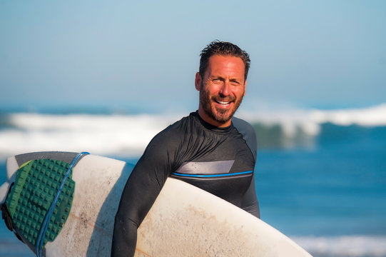 natural portrait of attractive and happy surfer man on his 40s carrying surf board after surfing morning at beautiful beach in wetsuit smiling enjoying Summer holiday