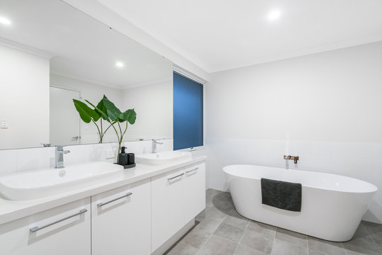Large modern bathroom interior with high end fittings and stand alone bathtub. PERTH, AUSTRALIA. MAY 2019.