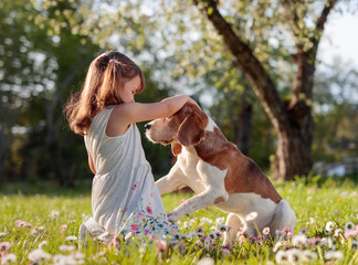 Happy little girl playing with dog in garden.