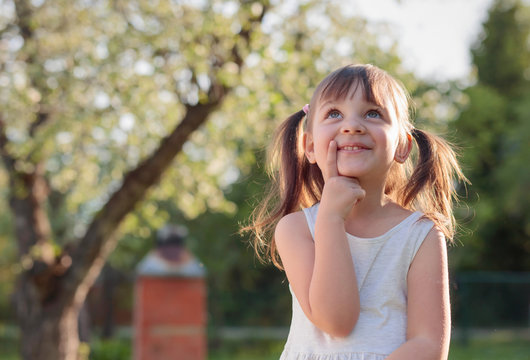 Happy little girl dreaming in the garden.