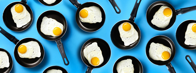 Creative food pattern with fried eggs on pans over blue background. Top view. Creative pattern in minimal style. Flat lay. Banner