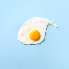 One fried egg on yellow paper background. Creative food concept in minimal style. Top view. Square...