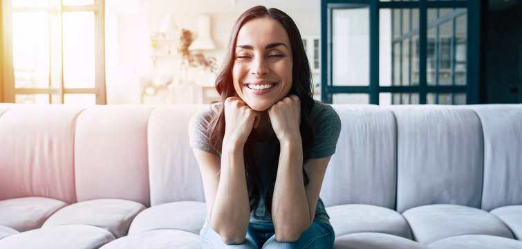 Portrait of smiling happy cute woman with closed eyes sitting on the couch at home