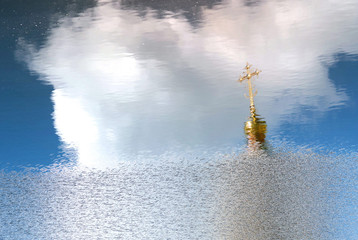 Golden dome and orthodox cross reflected in water surface. Blurred blue sky reflection in background. Copy space