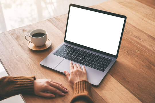 Mockup image of a woman's hand using and touching on laptop touchpad with blank white desktop screen with coffee cup on wooden table