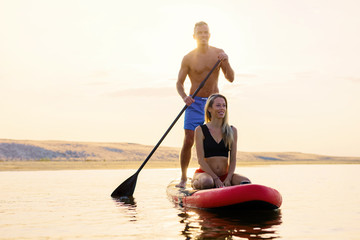 Couple relaxing together on paddle board