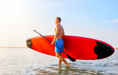 Man walking in the water with SUP board