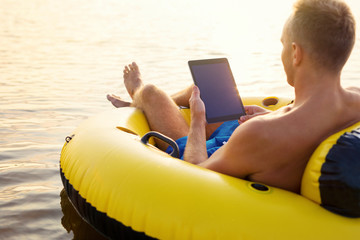 Man using tablet while relaxing in the water