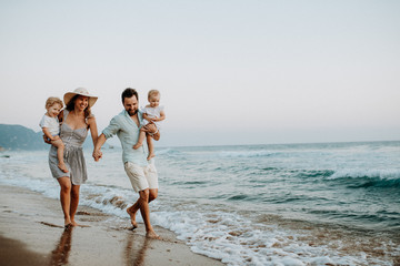 A family with two toddler children walking on beach on summer holiday at sunset.