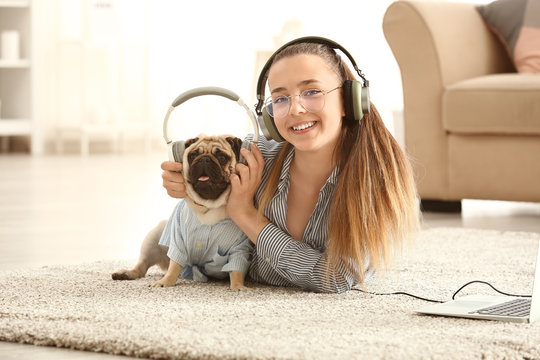 Teenage girl with cute pug dog listening to music at home