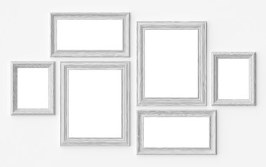 White wooden picture or photo frames on white wall with shadows