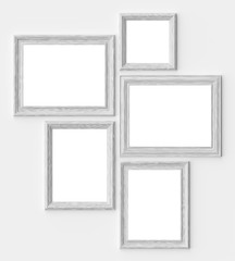 White wood picture or photo frames on white wall with shadows with copy-space