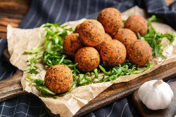 Tasty falafel balls and arugula on board