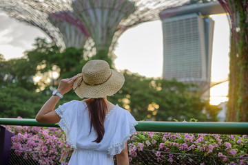 Fototapete - Young Woman traveling with white dress and hat, Asian traveler looking to supertree at gardens by the bay in Singapore. landmark and popular for tourist attractions. Southeast Asia Travel concept