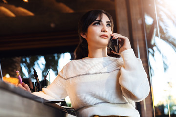Young woman talking on cell phone while sitting alone in coffee shop.Smiling girl has telephone conversation while resting in cafe