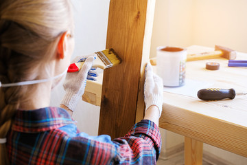 Repairman, carpenter, hired worker applies a protective varnish or paint brush on a wooden Board. Hands in gloves holding a brush in paint. The concept of home and professional repair, construction.