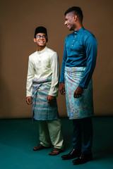 A young Malay and Indian men smile and laugh as they stand next to one another in a studio. They are both Muslims preparing to celebrate Ramadan and are both wearing traditional baju melayu clothing.