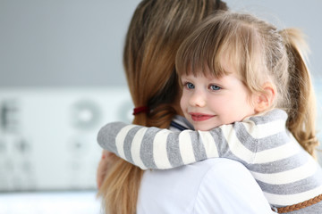 Cute little girl hugging female doctor in her office portrait