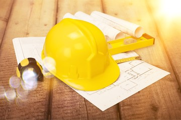 Yellow hard hat and blueprints on wooden desk in a construction concept
