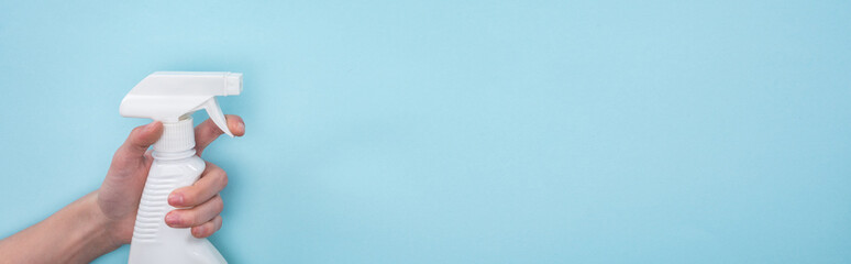 panoramic shot of woman holding white spray bottle with detergent on blue background