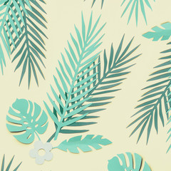 Wall Mural - Turquoise green tropical leaves on pastel yellow background, top view, flat lay. Creative botanical layout