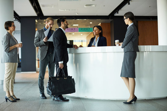 Handsome mixed race businessman with travel bag standing at registration counter and talking to receptionist while checking in to hotel