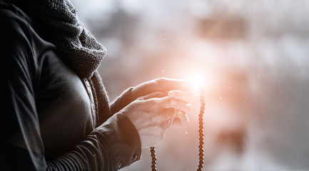 Foto En Lienzo - Woman hands praying and holding a beads rosary with Jesus Christ on lighting backgrouns, black&white, religious faith concept