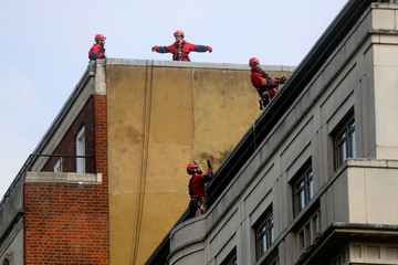 Greenpeace activists prepare to abseil down the facade of the BP headquarters in London