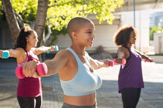 Three curvy women exercising with dumbbells
