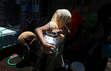 A woman carries a metal pitcher filled with free drinking water on a hot summer day in Ahmedabad