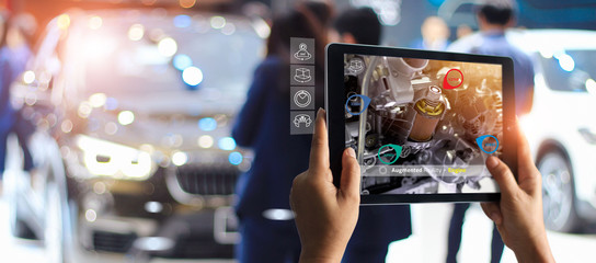 Augmented reality concept. AR. Industrial 4.0 , Hand of engineer holding tablet using virtual AR service application to check the work of electric machine on car showroom background Fototapete