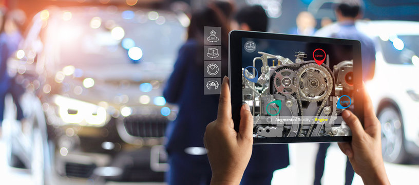Augmented reality concept. AR. Industrial 4.0 , Hand of engineer holding tablet using virtual AR service application to check the work of electric machine on car showroom background