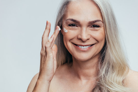 Senior woman applying anti aging cream