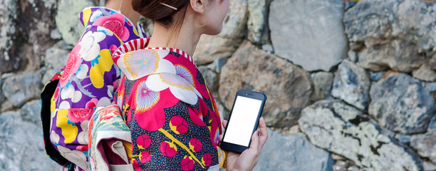 Young girl wearing Japanese kimono  using smartphon with blank white screen background searching or use application concept. Wall mural